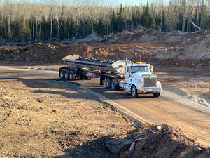 Large hauling truck filled with rock on a dirt road.
