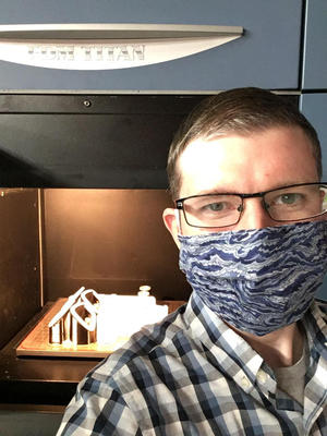 Man wearing face mask stands in front of machine with plastic parts visible