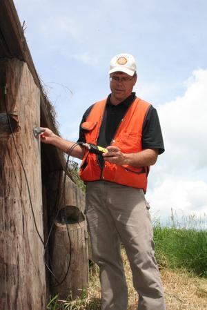 Mann in orange safety vest stands next to wood bridge supports.