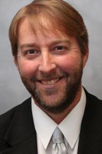Headshot of man in suit.