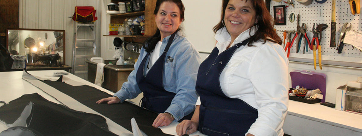 Two women in blue aprons in a sewing operation standing at the cutting table.