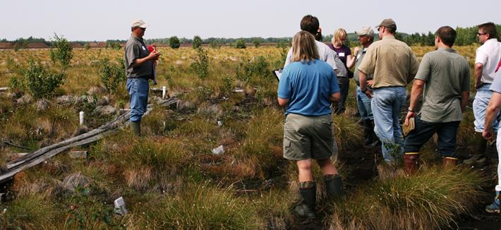 People standing in a bog listening to one person.