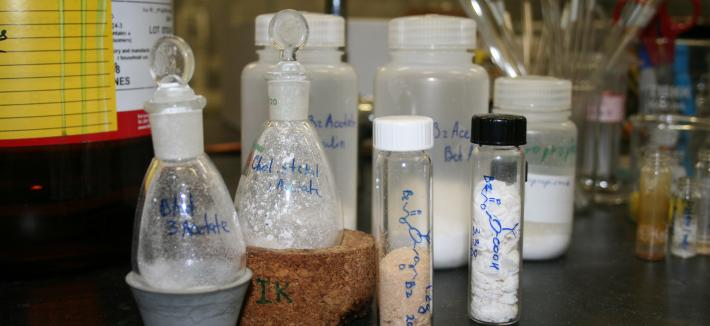 Close-up of glass vials with chemical description and powder inside