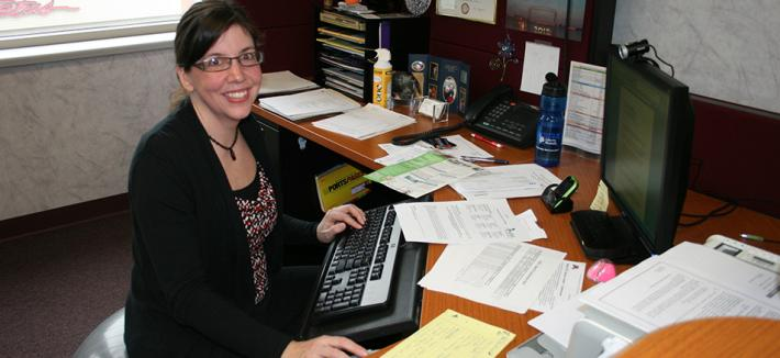 Dark haired woman sitting at office desk.