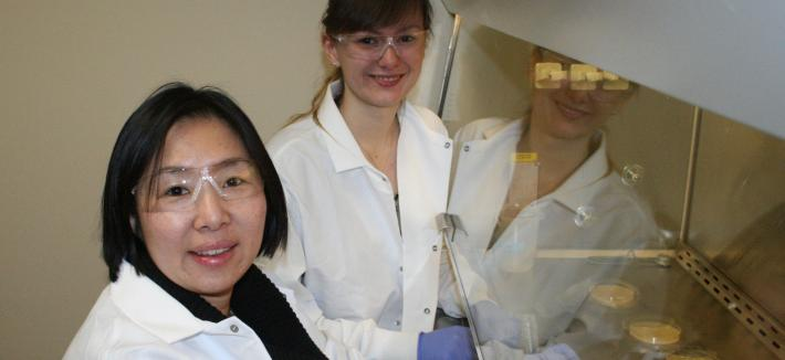 Two women in white lab coats and safety glasses by a large machine.