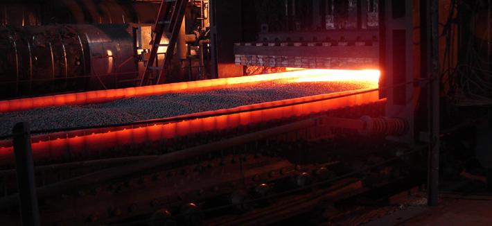 Taconite pellets on a flat moving bed coming out of a red hot furnace.