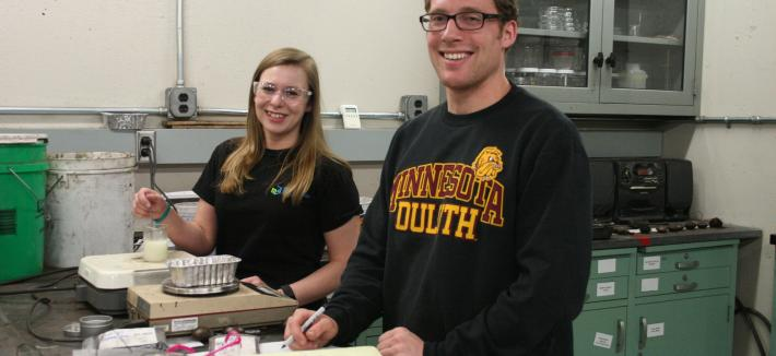 A female and male standing behind a lab bench.