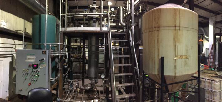 Processing machinery with stairs up the middle and a big white tank to the right