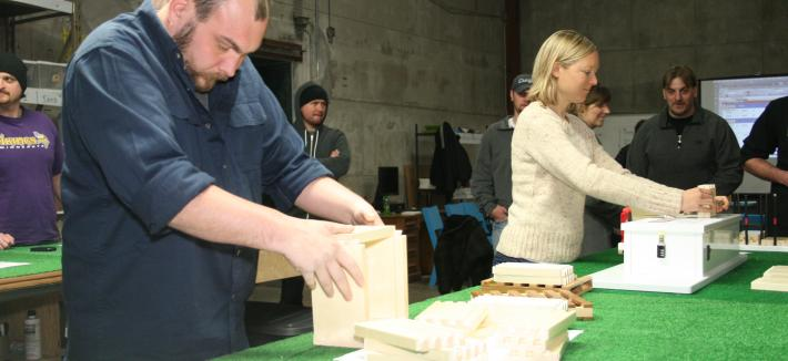 A man and a woman standing at a table and stacking rectangular pieces of wood.