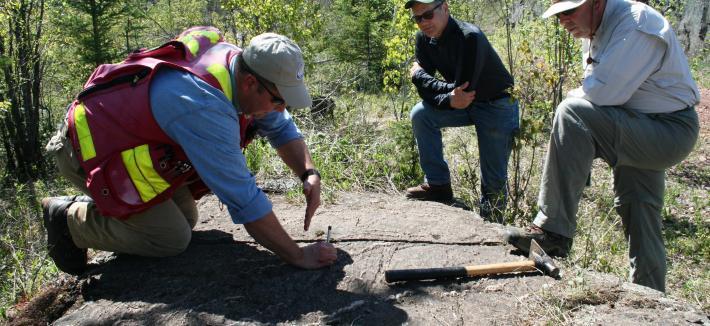 Three men examining a rock outcrop