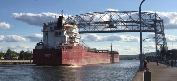 Large red ship passes under metal structure bridge
