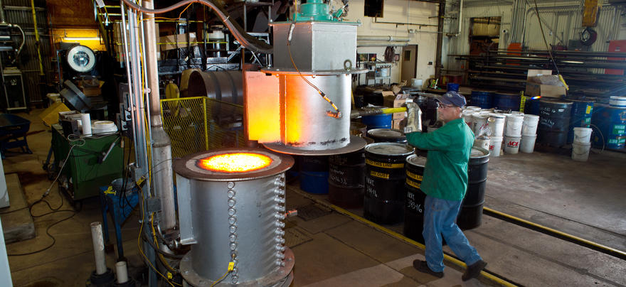 Man in industrial setting moves equipment with hot, glowing embers.
