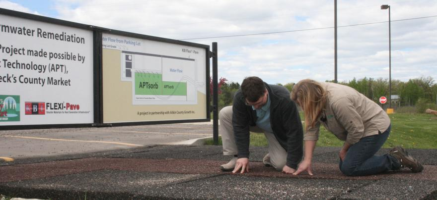 A man and a woman kneeling over and looking into a drainage system.