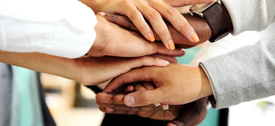 Hands of a variety of people stacked on top of each other.
