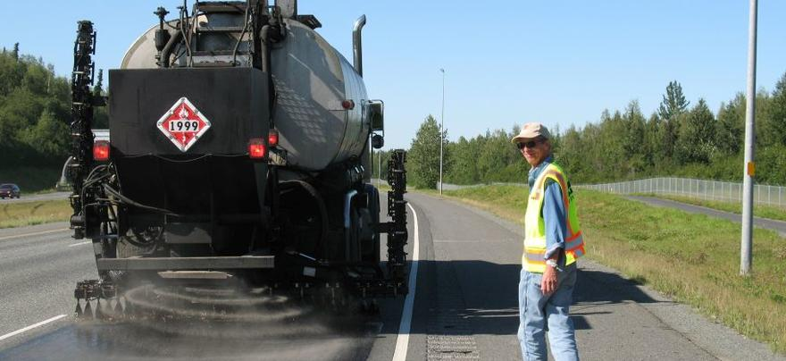 Gravel being spread out back of truck onto road, man walks alongside