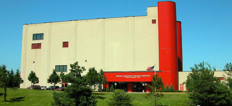 Photo of large tan colored building with a red tower on the right side.
