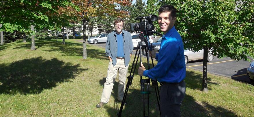 Man in front of news camera outdoors, reporter behind camera smiles back