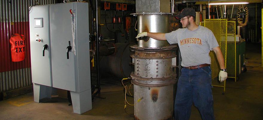Man operates upright cylindrical machine.