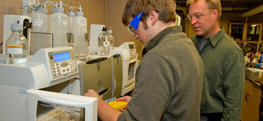 Two men wearing safety glasses in a lab operating analysis machinery.