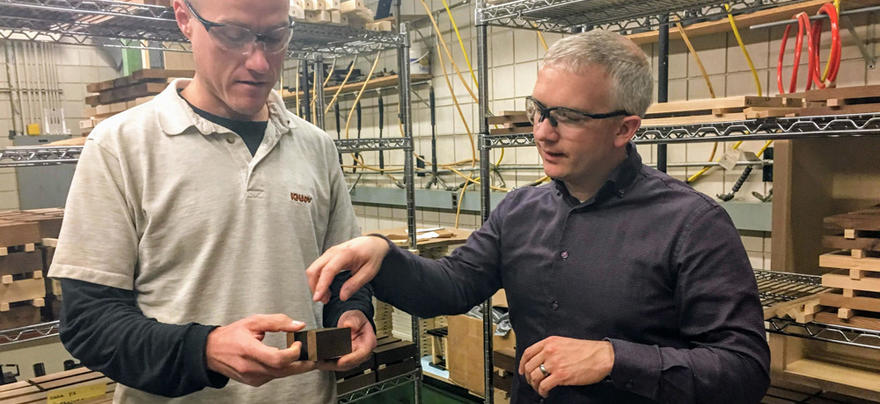 Two men discuss the qualities of thermally modified wood in a research lab.