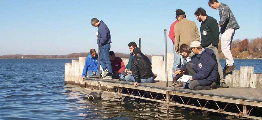 A dozen people on a dock in the water, some sitting, some standing