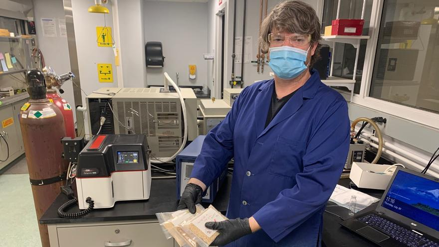 Man in blue lab coat in lab setting holds four clear packets containing wood chips