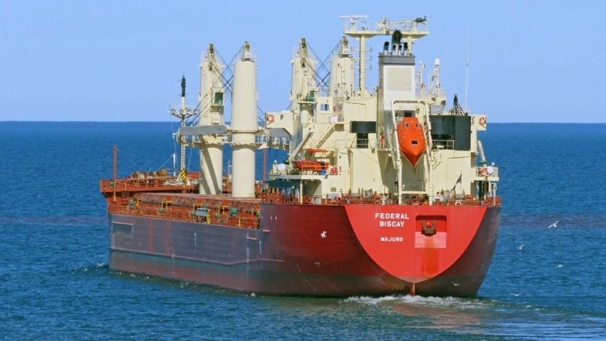 Large red ocean-going ship viewed from behind on water.