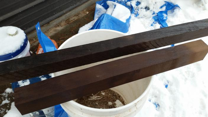 Two lengths of wood, one dark brown, one almost black, are posed on a white bucket.