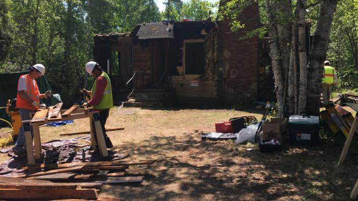 Two men in construction gear work outside a partially torn apart house structure.