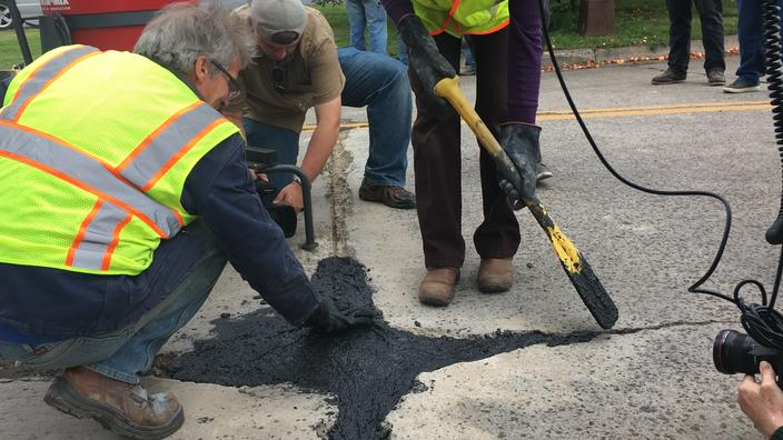 A man in a yellow vest kneels as he smooths black material with a gloved hand on a cement street.