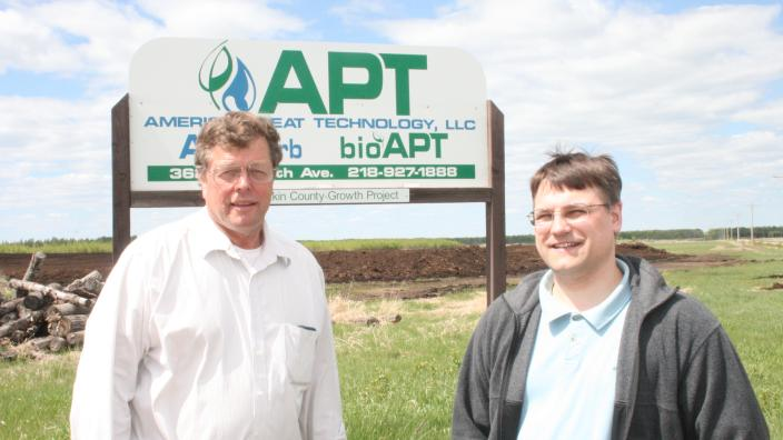 Two men stand outdoors in front of a business sign