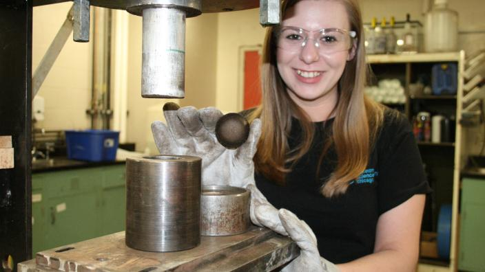 Woman is framed by machinery, holding a small brown disk