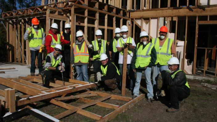 A dozen men in construction attire pose in front of a partially constructed structure.