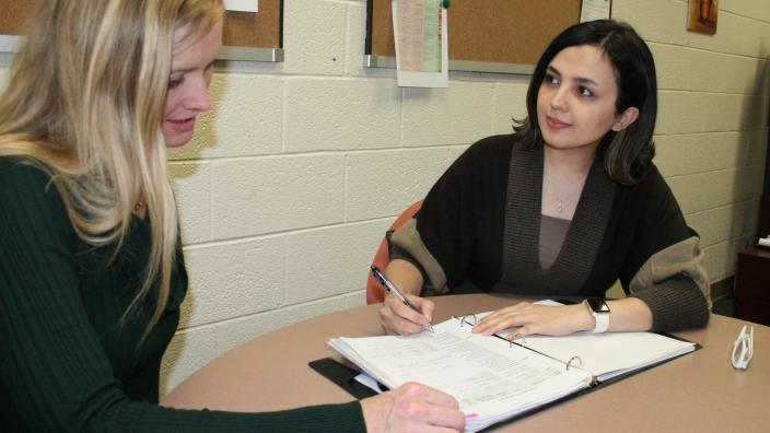 Two women sitting at a table with 3-ring binder in discussion.