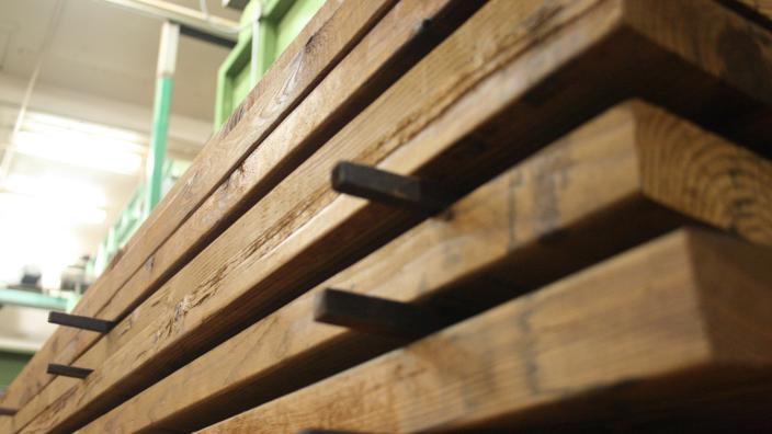 Close image of stacked dark brown lumber