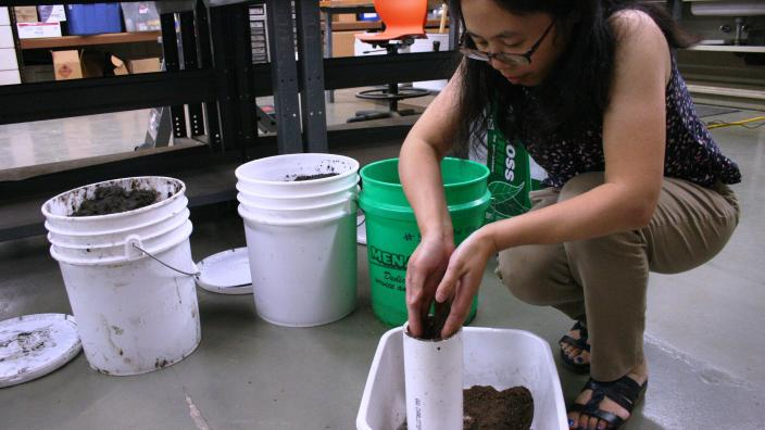Woman in lab kneels to fill white tube with dirt