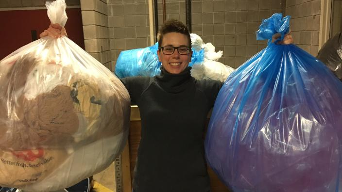 Woman smiles while holding two large bags filled with plastic.