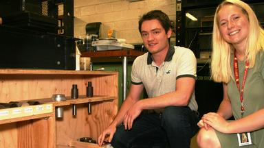 A male and female are kneeling next to wooden shelving in an industrial setting