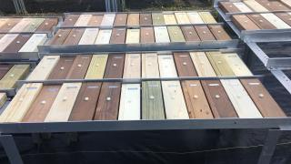 Rectangles of wood of varying colors sit in rows on outdoor shelves.