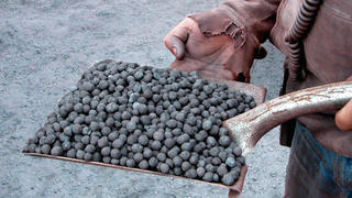 Shovel head filled with taconite pellets held by a man.