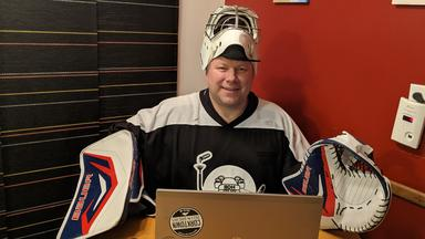 Man dressed in hockey gear stands behind a lap top computer