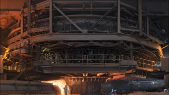 Industrial scene of large glowing furnace, person in front dwarfed by machinery.