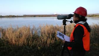 Woman in safety vest and hard hat looks through telescope at dawn by water body.