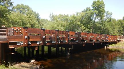 Wood bridge extends across a small river.