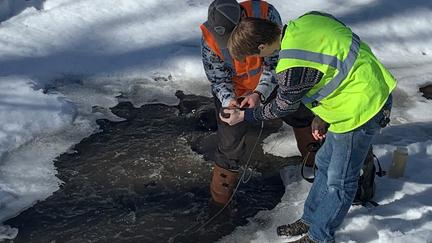 Two men wearing safety vests stand on frozen stream bent over hole in ice.