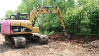 An excavator in operation on a dirt road digging a ditch