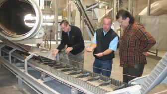 Three men looking at white product on conveyor belt production line.