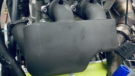 Black engine part installed on snowmobile engine