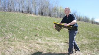 Man outdoors holds a black airplane-like contraption ready to launch.