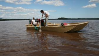 Three males in a low profile boat on a large lake, two males dropping a tool into the water.